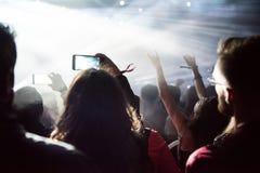 享受一个电子音乐会的人人群在节日 库存照片