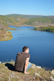 享受一个美丽的湖的看法的年轻人 免版税库存照片