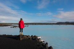 享受一个蓝色盐水湖的看法的冰岛顶蚀作用的一个女性远足者 免版税库存照片