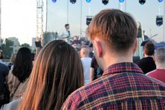 享受一个音乐会的年轻夫妇在一个晴朗的夏天晚上 免版税库存图片