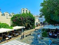 享受一个晴朗的夏日的人们在室外餐馆在市场大厅在老镇在Kos海岛上的Kos镇  库存图片