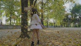 享受一天的亭亭玉立的式样女孩在微笑和转动在落的秋叶中的公园享受在慢动作的自由- 股票录像