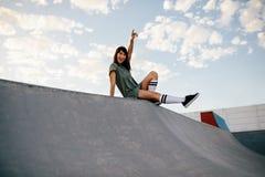 享受一天的女性溜冰板者在冰鞋公园 图库摄影