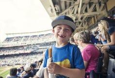 享受一天的年轻男孩观看一场职业棒球比赛 免版税库存照片