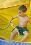 享受一张湿可膨胀的幻灯片的男孩 免版税库存图片