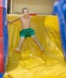 享受一张湿可膨胀的幻灯片的男孩 免版税库存照片