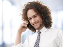享受一次电话交谈的年轻英俊的人 图库摄影