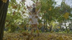 享受一美好的秋天天和转动在从树的落的黄色叶子中的亭亭玉立的欧洲女孩在慢动作- 股票录像