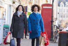 享受一起购物的两个成熟女性朋友在城市 免版税图库摄影