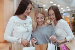 享受一起购物的年轻女人在购物中心 免版税库存图片