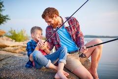 享受一起钓鱼的父亲和儿子 免版税库存照片