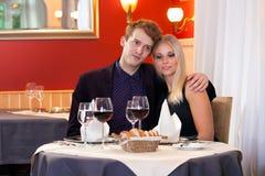 享受一顿浪漫晚餐的爱恋的夫妇 免版税库存照片
