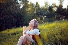 享受一顿野餐本质上的美丽的少妇 女孩坐草,休息,放松 库存图片