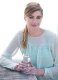 享受一份凉快的刷新的饮料的端庄的妇女  免版税库存照片