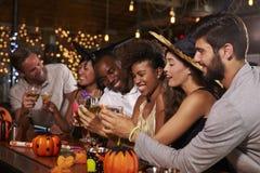 享受万圣夜的朋友集会在做多士的酒吧 免版税库存图片