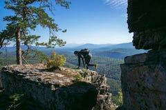 享受上升的妇女远足者在一座山的上面在晴朗的夏日 免版税图库摄影