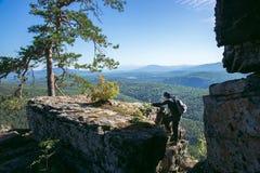 享受上升的妇女远足者在一座山的上面在晴朗的夏日 免版税库存照片