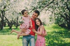 享受与两个孩子女儿的父亲春天步行 与两个姐妹的家庭 图库摄影