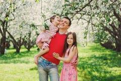 享受与两个微笑的孩子女儿的父亲春天步行 库存图片