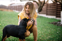 享受与快乐的rottweiler小狗的妇女时间 免版税库存照片