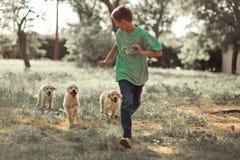 享受与最好的朋友狗象牙白色拉布拉多小狗的猎犬小狗可爱的场面handsom青少年的男孩夏时假期 愉快的ai 免版税库存照片
