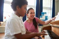 享受与老师的男学生钢琴课 免版税库存图片