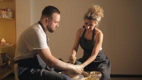 享受与黏土一起使用的年轻夫妇在瓦器车间 股票录像