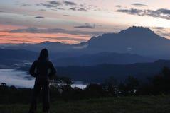 享受与登上Kinaba的妇女的Sillhouette早黎明 免版税库存照片