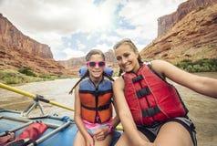 享受乐趣白浪漂流旅行的活跃年轻家庭 免版税库存图片