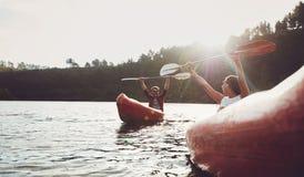 享受乘独木舟的愉快的年轻夫妇在夏日 免版税库存图片