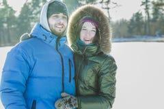 享受了不起的冬天的年轻夫妇户外一起在晴天 免版税库存图片
