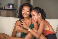 享受互联网社会媒介的年轻美丽和愉快的亚裔女朋友夫妇或姐妹获得乐趣与手机一起 库存图片