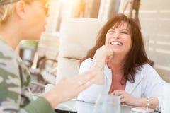 享受交谈的两个女性朋友外面 免版税库存图片