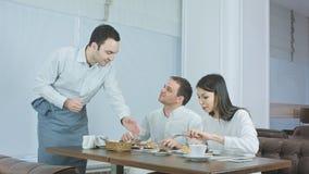 享受他们的午餐的年轻夫妇在餐馆,当带来更多食物的侍者 图库摄影