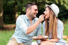 享受他们的时间的爱的年轻夫妇在公园,有一顿偶然浪漫野餐 免版税图库摄影