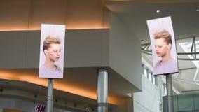 享受他们购物的旅行的人们在主要大厅里有促进在购物中心的屏幕顶视图大品牌千年 影视素材