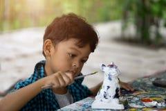 享受他的与油漆刷的亚洲孩子绘画 免版税图库摄影