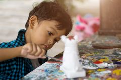 享受他的与油漆刷的亚洲孩子绘画 免版税库存照片