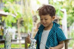 享受他的与油漆刷的亚洲孩子绘画 免版税库存图片