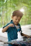 享受他的与油漆刷的亚洲孩子绘画 库存图片