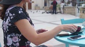 享受休息的妇女在街市街道咖啡馆,看通过笔记本页 股票录像