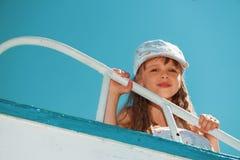 享受使用在小船的小逗人喜爱的女孩画象  免版税图库摄影