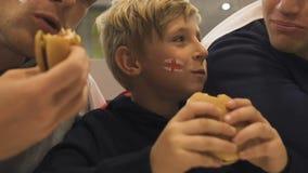 享受便当膳食的愉快的英国爱好者在紧张的足球比赛,胜利以后 股票视频