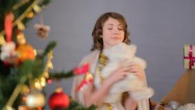 享受假日和跳舞与玩具的逗人喜爱的女孩在圣诞树,童年附近 影视素材