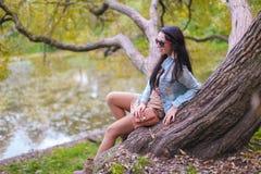 享受假日的年轻逗人喜爱的女孩在秋天公园 免版税库存照片