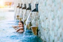 享受假期假日的妇女在与游泳池的豪华海滩前的旅馆手段和热带lansdcape在附近 免版税库存照片