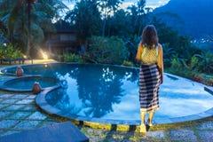 享受假期假日的妇女在与游泳池的豪华海滩前的旅馆手段和热带lansdcape在附近 库存图片