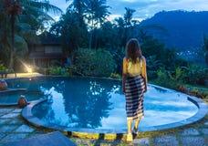 享受假期假日的妇女在与游泳池的豪华海滩前的旅馆手段和热带lansdcape在附近 图库摄影