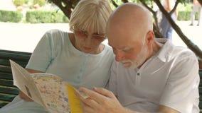 享受假期的家庭 前辈坐长凳在学习城市地图的公园寻找名胜地 影视素材