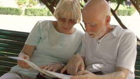 享受假期的家庭 前辈坐长凳在学习城市地图的公园寻找名胜地 股票视频